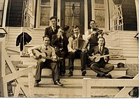 "1937 B&W photograph of Donn Reynolds (top left) as ""The Yodeling Ranger"" seated on steps with his band (Winnipeg, Manitoba, Canada)."