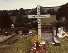 A simple white cross engraved with a memorial message to Thomas stands in a grave yard surrounded by hills