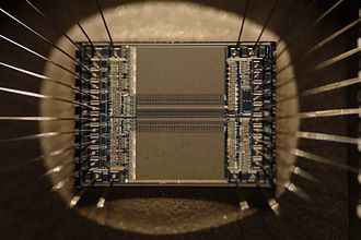 Integrated circuit - Integrated circuit from an EPROM memory microchip showing the memory blocks, the supporting circuitry and the fine silver wires which connect the integrated circuit die to the legs of the packaging.