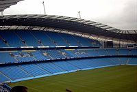 Roughly the same camera position shows grass up to the blue seats of the stands. The stand is now split into three levels of permanent seating.