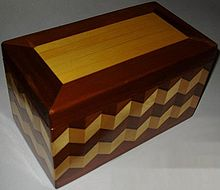 A Storage Box Made Of Wood, With An Elaborate External Wood Stain Design