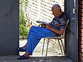 Elderly Man Reading at Gate - Tirana - Albania (41002643010).jpg