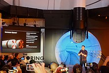 Musk speaks to a crowd of journalists. Behind him is a lighted tunnel.