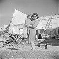 Emigrantenvrouw met kind op de arm temidden van vernielde huizen en wasgoed dat , Bestanddeelnr 255-1201.jpg