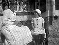 En kvinna med en korg i knät och en flicka sitter på en bänk vid en husgrund - Nordiska Museet - NMA.0057511.jpg
