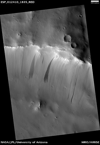 Dark slope streak - Dark slope streaks are often fan-shaped with multiple fingers (digitation) at their downslope ends. Image is from the HiRISE camera on the Mars Reconnaissance Orbiter.