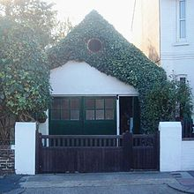 An extremely small workshop adjoining a house and standing behind a wooden gate with white gateposts. It has green double doors with an open door to their right.  Above this is a white-painted wall which is heavily draped with ivy, although a circular louvre is clearly visible through this.  The roof is steep and pointed.
