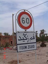Entrance to Foum Zguid with sign in Roman and Arabic alphabets.