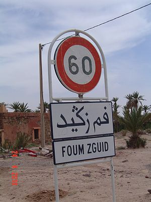 Foum Zguid - Entrance to Foum Zguid with sign in Roman and Arabic alphabets.