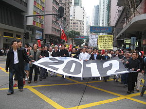leaders of a protest march holding open a large banner with the figure '2012' in black-and-white print