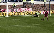Een voetballer scoort een doelpunt tegen de doelman van de tegenstander uit een strafschop.  Stewards en camera-operators zijn zichtbaar achter het doelnet.