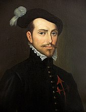 "Old painting of a bearded young man facing slightly to the right. He is wearing a dark jacket with a high collar topped by a white ruff, with ornate buttons down the front. The painting is dark and set in an oval with the letters ""HERNAN CORTES"" in a rectangle underneath"