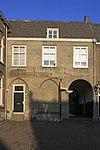 foto van Woonhuis tegen de noordgevel van de Augustijnenkerk in de hoek tussen het schip dezer kerk en de kloostergang. Lijstgevel, late Empire ramen en schilddak.
