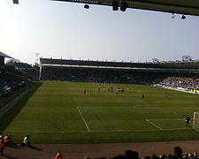 A panorama of a semi-full football stadium with green seats on a sunny day.