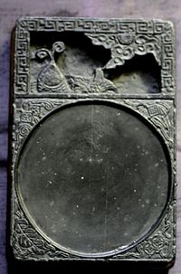 A black, rectangular stone tablet with two sections. The top quarter section contains a carving of a fish, and the bottom three fourths contain a shallow, circular indent for the ink.