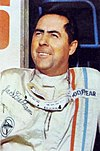 Jack Brabham wearing a racing suit and smiling upwards