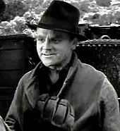 Head and shoulders shot of Cagney, wearing black fedora and smiling slightly, scenery in the background