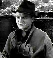 Head and shoulders shot of Cagney, wearing black fedora and smiling slightly; scenery in the background.
