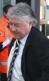 A grey-haired man in a black suit walks out of a building.