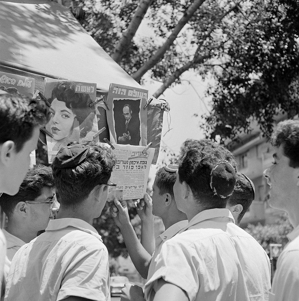 Joodse jongemannen met keppeltjes staan voor een kiosk en houden een krant met d, Bestanddeelnr 255-1848