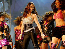 A medium shot of a woman dancing amid several other women. The woman in the centre is dressed in a black and silver outfit, while the women around her are dressed in pink and black clothing.