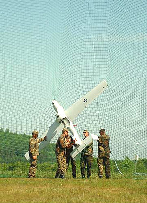 A German Army unmanned aerial vehicle, known as LUNA, is recovered from its net following its fly-over mission
