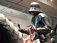 An dummy wearing 15th-century armour and holding a mace in its right hand