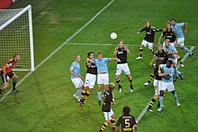 An action shot of two competing football teams trying to win a flying ball in the penalty area of one of the teams, the ball is heading for the head of the attacking teams captain. The players of the attacking team are wearing sky-blue shirts, white shorts and sky-blue socks. The field players of the defending team are wearing black shirts, white shorts and black socks. The goalkeeper for the defending team is wearing an orange shirt, black shorts and black socks.