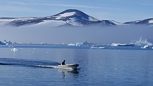 Melville Bay - An Inuit hunting boat in southern Melville Bay. Late morning fog and icebergs in the background.