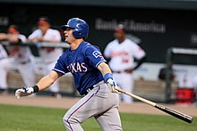 Michael Young, wearing a blue batting helmet and baseball jersey with the lettering TEXAS across it and the Flag of Texas on the left sleeve, clutches a baseball bat in his left hand and looks towards the left after hitting a baseball.