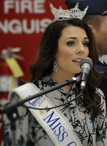 A young woman with brown hair, wearing a crown on her head and a Miss Oregon sash over her dress, singing into a microphone
