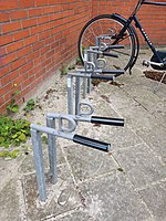 An example of a common type of front-wheel-only bike stand in the Netherlands. No danger of wheel bending, with a loop for attaching a lock.
