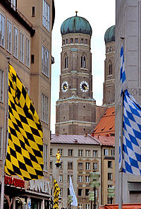 Banners with the colors of Bavaria (right) and Munich (left) with the Frauenkirche in the background.