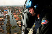 A Coast Guard helicopter crew member looks out over post-Katrina New Orleans