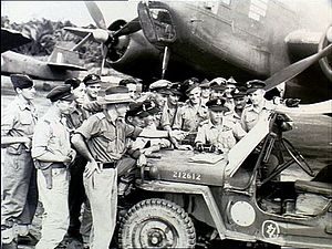Approximately 15 men wearing military uniforms in discussion around a jeep, parked in front of a twin-engined aircraft