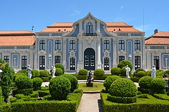 Palace of Queluz - By an unknown architect, the façade of the ballroom wing with its ogee arch is reminiscent of Borromini. This wing with its varying rooflines and swooping pediments illustrates the palace's appearance as a series of pavilions and wings rather than one large mass (see key 6). To the left can be seen the five-stage campanile with floral finials in the town square beyond the cour d'honneur.