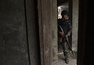 Philippine National Police Maritime Group - PNP Maritime Group member waits to clear rooms of an abandoned hotel