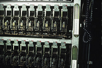 Stepping switch - An array of uniselector stepping switches as installed in a telephone exchange. The silver dials show the current position of the moving wipers. The fixed feeder brushes are barely visible.