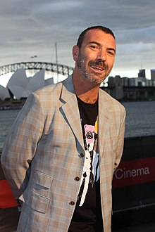 A 46-year-old man is shown in a three-quarter shot. He is leaning slightly to his left. He wears a peppery beard with very short hair and is smiling with his arms behind. His coat is checked grey and brown which obscures his black tee-shirt and its cartoon print. In the background is the Sydney Opera House and Harbour Bridge with Port Jackson behind him. The sky is overcast.