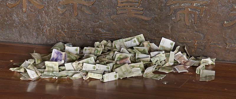 Assorted bills in a pile on a wooden floor