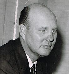 Candid black and white head and shoulders photograph of Ivy wearing a dark suit and looking down slightly