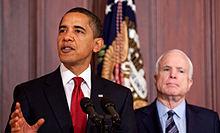 Barack Obama parolante en malfono ĉe endoma okazaĵo kun amerika flago en fono; John McCain malantaŭ li, iom de fokuso