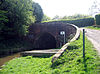 The canal enters the tunnel through and arch and on the right a road curves towards the left to cross the bridge.