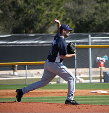 A man throwing a baseball wearing a navy-blue baseball jersey and cap and gray baseball pants