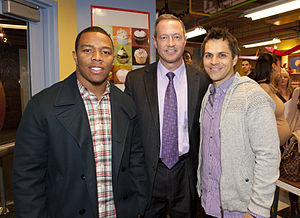 Three men stand together and smile. The man on the left is African American and wearing a plaid shirt with a black jacket. The man in the center is Caucasian and wearing a black suit with a light purple shirt and a dark purple tie, while the man on the right is Caucasian and wearing a purple checkered shirt with a grey sweater. A poster of cupcakes is visible on the wall behind them. People are talking to each other in the background.