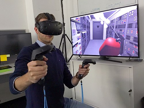Researchers with the European Space Agency in Darmstadt, Germany, equipped with a HTC Vive head-mounted VR headset and motion controllers, demonstrates how astronauts might use virtual reality in the future to train to extinguish a fire inside a lunar habitat Reality check ESA384313.jpg