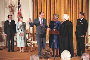 William Rehnquist - William Rehnquist (left) takes the oath as Chief Justice from retiring Warren Burger at the White House in 1986, as his wife, Natalie, holds a Bible, President Ronald Reagan and Justice Antonin Scalia look on