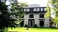 Blanka domo kun malhela tajlado, inkluzive de dekoraciaj elementoj. La domo havas tri rakontojn, kaj ekzistas okangula elemento protrudanta super la supra etaĝo.
