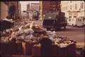 SANITATION DEPARTMENT TRUCK PREPARES TO HAUL ACCUMULATED TRASH FROM STREET. BANNER IN BACKGROUND REMINDS CITIZENS... - NARA - 545502.tif