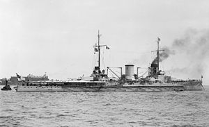 A large warship sits motionless off shore, light gray smoke drifts lazily from its forward smoke stack.